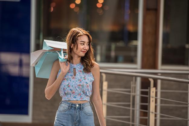 ショッピングコンセプト、モールセンターで買い物袋を保持しているアジアの女性に幸せな時間。