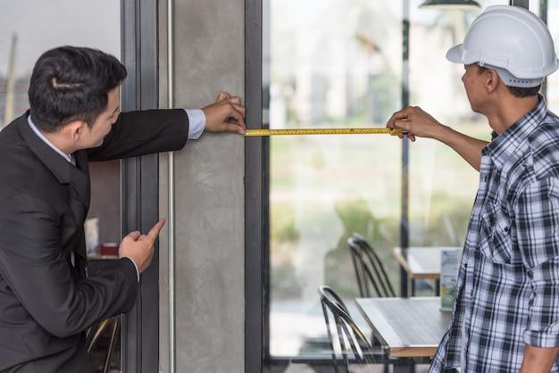 雇用主と現場のガラス窓を測定する職長。