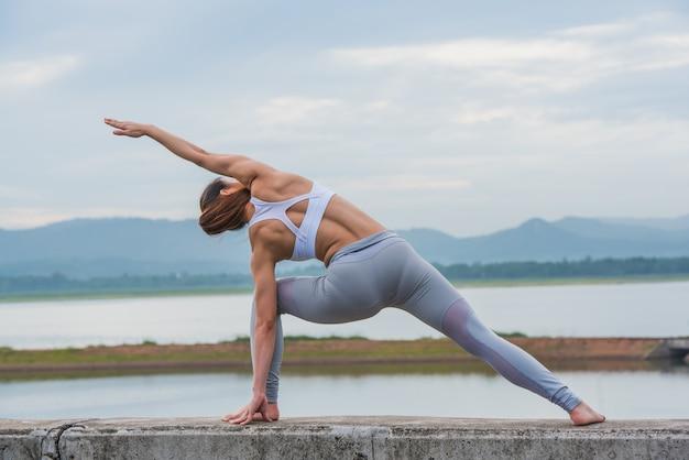 トレーニングヨガ、美しい山の湖の壁にヨガの練習を行う若い女性