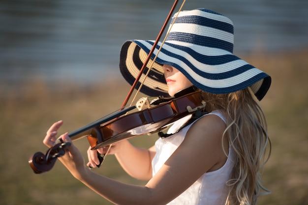 川のそばにバイオリンを弾く女性。