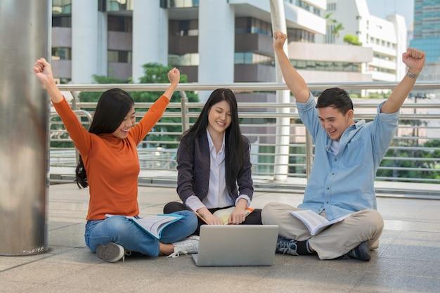 Молодые студенты учатся и читают вместе в университетском зале во время перерыва с книгами и ноутбуком
