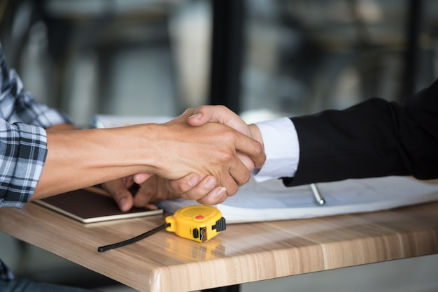 サイトの建物での会議で一緒に握手するビジネス人々。
