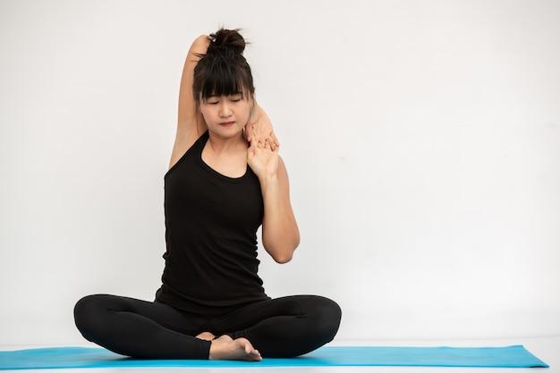 Женщина йоги йоги азиатская делая представление йоги дома.