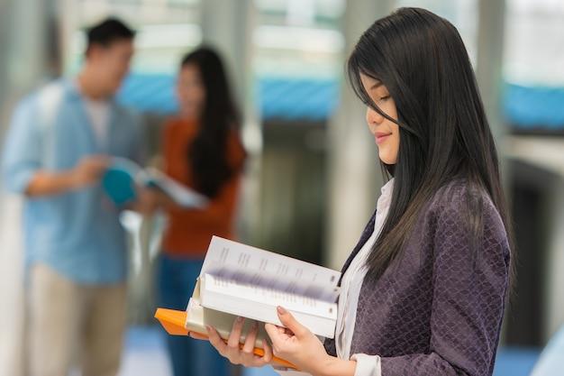 キャンパスで手に本を持つ若い女性学生。