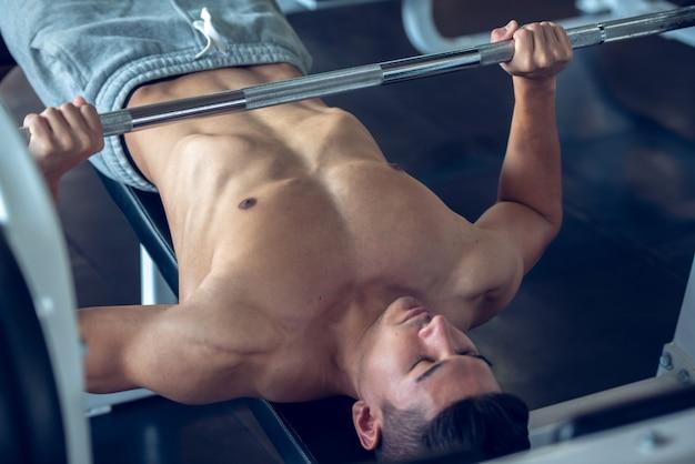 スポーツジムのベンチでバーベルの練習を行うスポーツ若い男