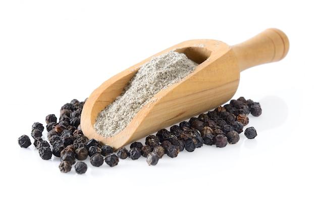 白の木製のスクープで黒胡椒粉末