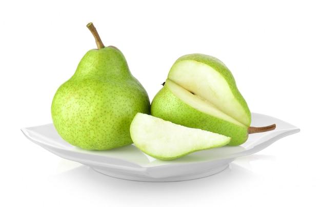 Зеленые груши в белой тарелке на белом фоне