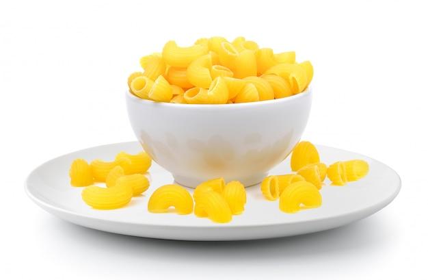 Сухие макароны в белой миске на белом фоне