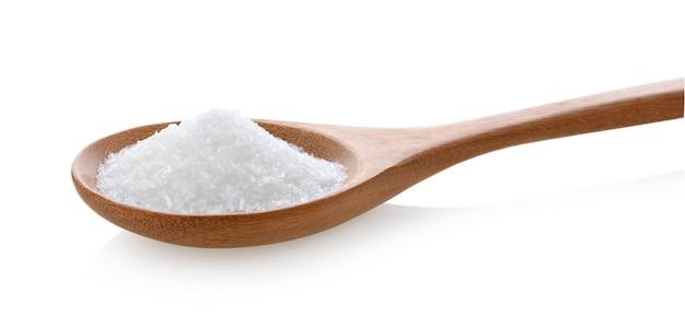 白い背景の木のスプーンのグルタミン酸ナトリウム