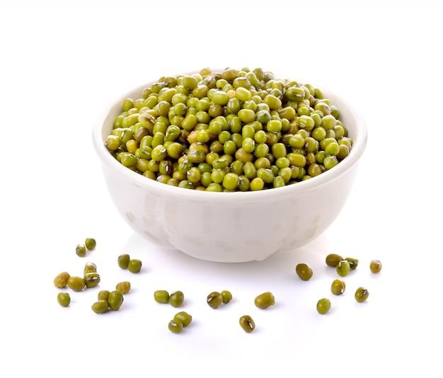 Зеленые бобы мунг в миске на белом фоне