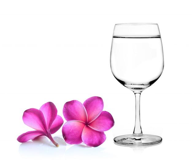 ガラスの水とプルメリアの花の白い背景の分離