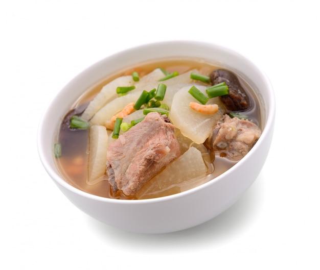 豚肉の大根のスープはボウル、白い背景で隔離のタイ料理に提供します
