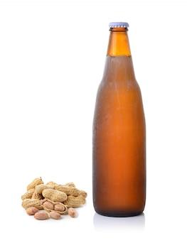 Арахис и пивная бутылка на белом фоне