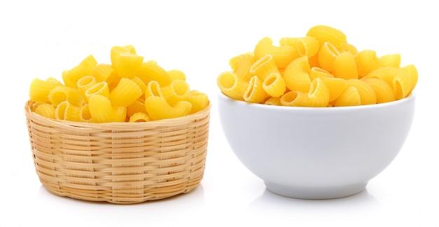 Сухие макароны в белой миске и корзине