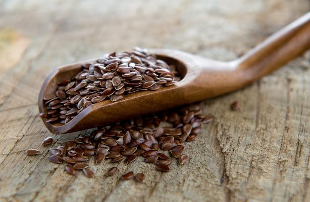 Льняные семена в деревянной ложкой на деревянный стол