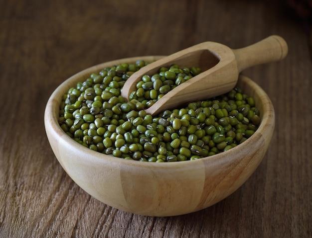 Зеленый грамм или бобы мунг в деревянной миске на столе