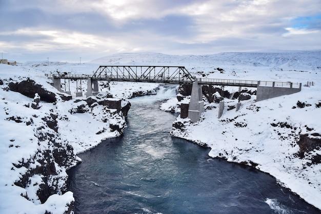 アイスランドで冬に覆われた雪と川を渡る橋。
