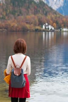 アジアの観光旅行者の女の子自由に平和を感じて湖に立っています。