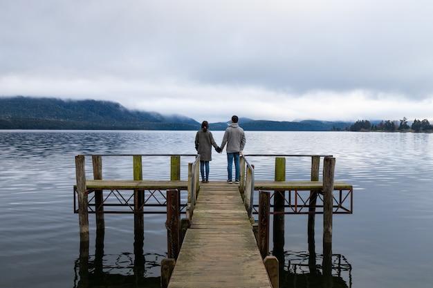 Молодая азиатская пара, держащая руки на мосту озеро те анау новая зеландия