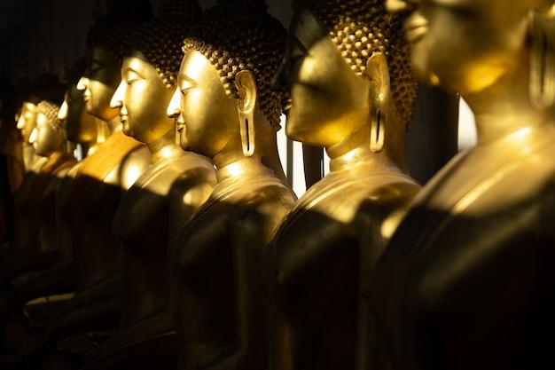 Закройте ряд золотой статуи будды в свете и тени солнца в храме ват пра шри махатхат