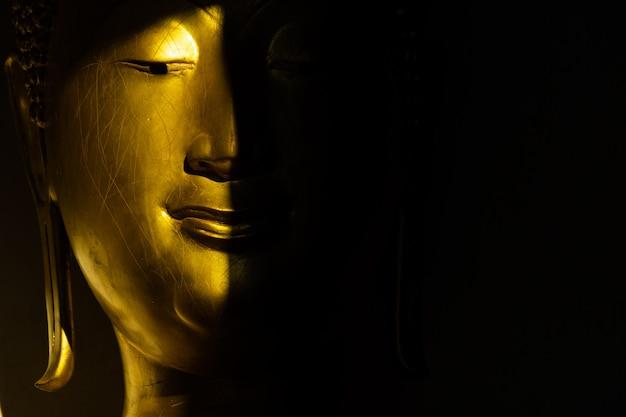 口を閉じて、ワットプラスリマハタート寺院で太陽の光と影で黄金の仏像を顔します。