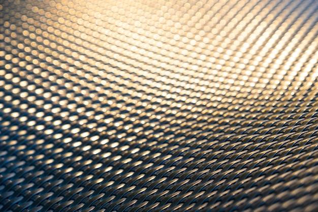 黄金の太陽の光の反射に籐の椅子の抽象的なパターンを閉じる