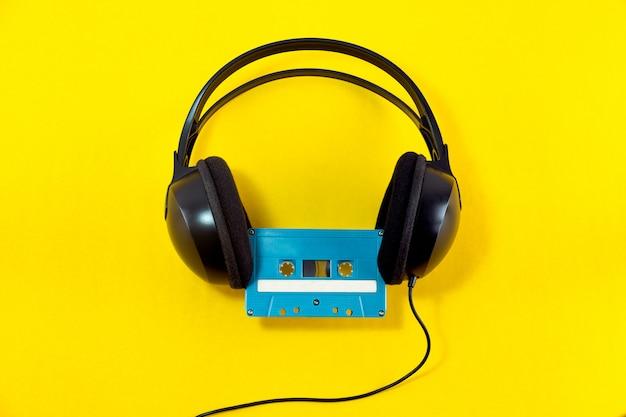 Взгляд сверху наушников и голубой классической кассеты ленты против желтой изолированной предпосылки