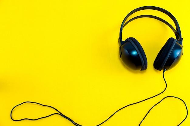 黄色の孤立した背景に対して黒のヘッドフォンのトップビュー