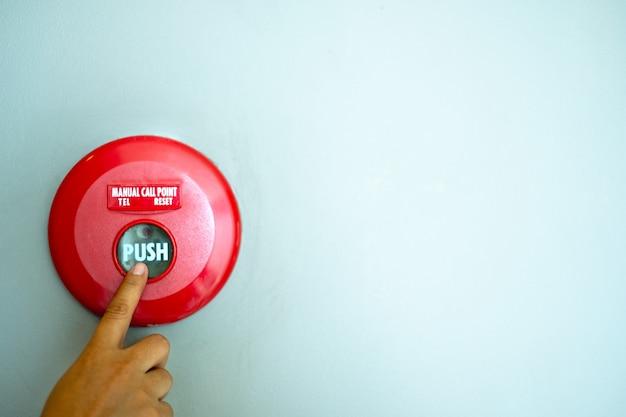 指は壁の背景に火災警報ボタン機器を押しています