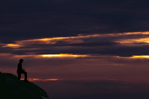日没時に空を背景に山に立っているシルエット男
