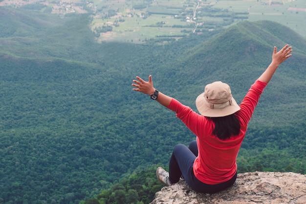 崖の上に座っている女性の後姿と山と木に対して手を押し上げる