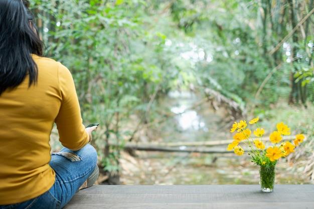 木製の桟橋に座っている女性は花を閉じる
