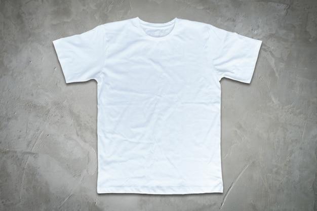 Белая футболка на фоне бетонной стены.