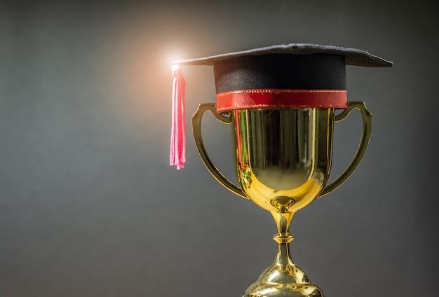 黄金のトロフィーを持つ卒業帽子
