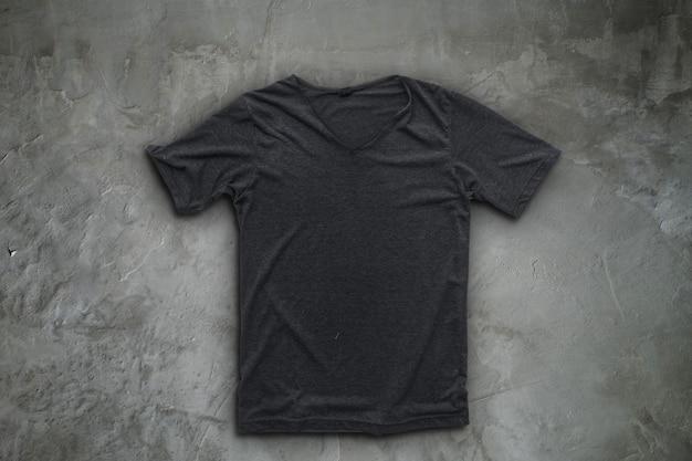 Серая футболка на фоне бетонной стены.
