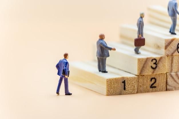 ミニチュアの人ビジネスマンは階段を歩く