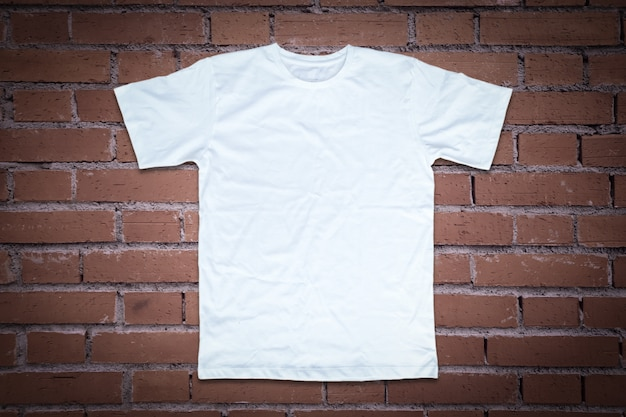 Белая футболка на фоне кирпичной стены.