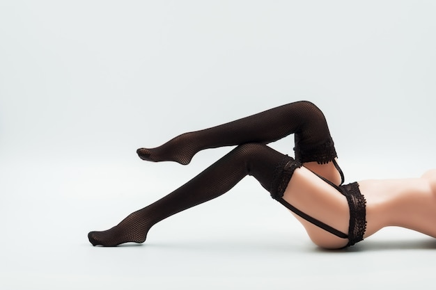 黒いレースのランジェリーとストッキングでセクシーなシリコーン人形の女性