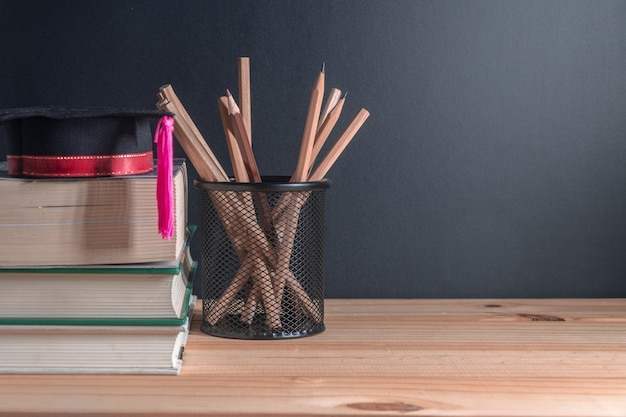 卒業帽子の上に木製のテーブルの本のスタック