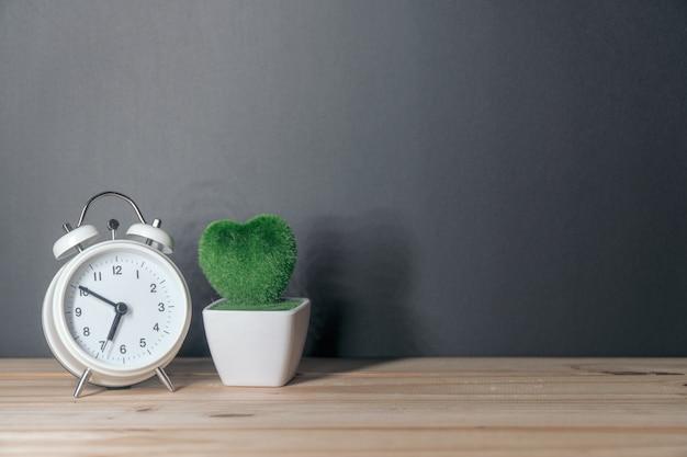 黒板の背景に木製のテーブルに目覚まし時計
