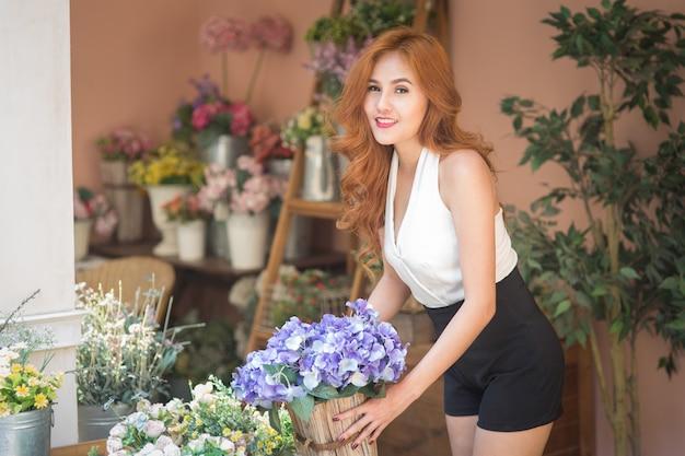 Улыбающаяся женщина флорист расставляет красивые цветы в цветочном магазине