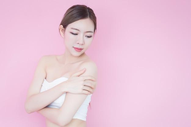 美しい若い白人アジアの女性は、清潔で新鮮な肌の顔自然化粧品で笑顔します。