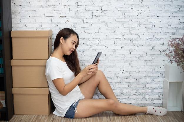 デジタルスマートフォンタブレットを使用して床に座って幸せな若い女性の肖像画