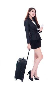 ホイールバッグで歩くと携帯電話を保持しているビジネス旅行でのビジネスの女性