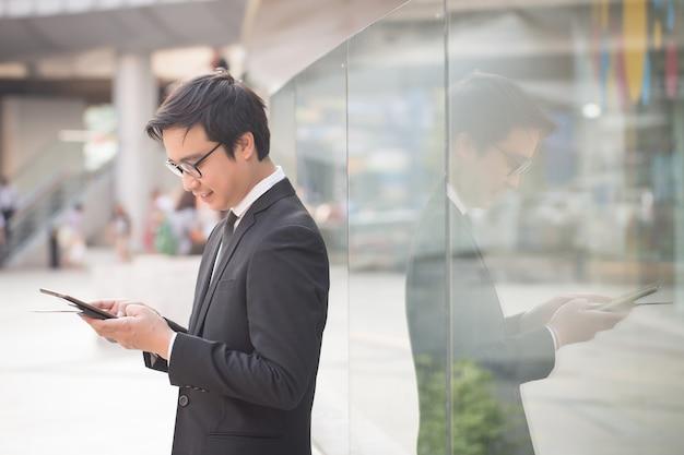 ビジネスの男性の笑みを浮かべての肖像画は、コンピューターのタブレットを使用して自信を持って見える