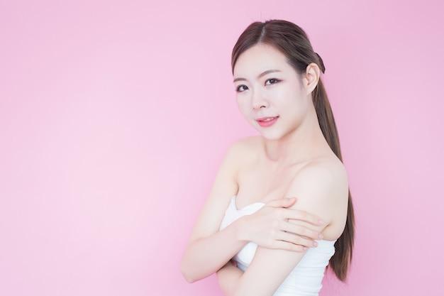 きれいな新鮮な肌の顔自然化粧品で美しい若いアジア女性笑顔