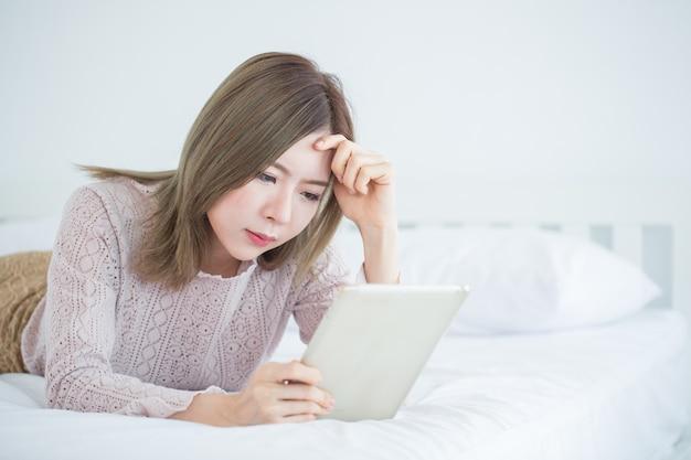 若いは、寝室にコンピューターのタブレットを探しているビジネス女性を強調しました。