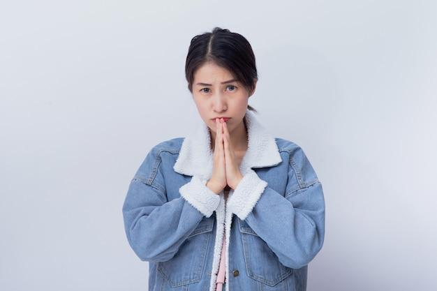 スタジオで青いカジュアルな服の肖像画を着ている若いアジアの女の子