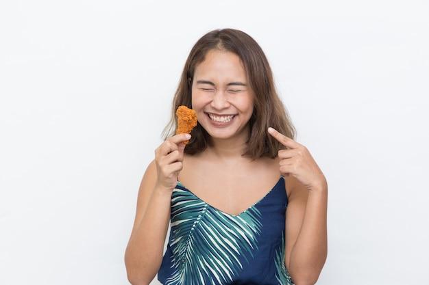 Молодая счастливая азиатская девушка держа куриную голень на белом с копией пространства