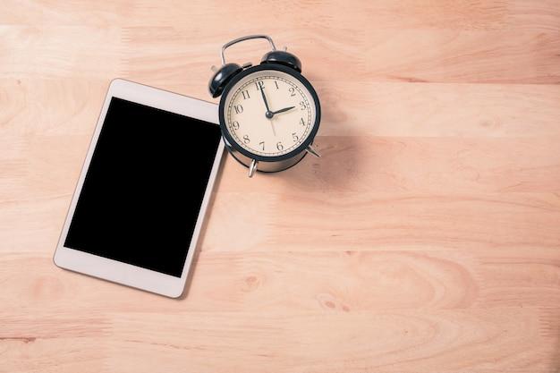 レトロな目覚まし時計とウッドバックグラウンドプロセスヴィンテージ色のデジタルタブレットのスマートフォン